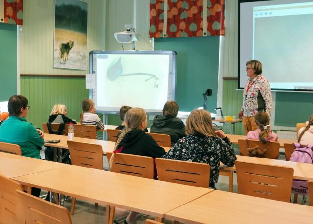 Nainen luennoi salissa istuville lapsille.